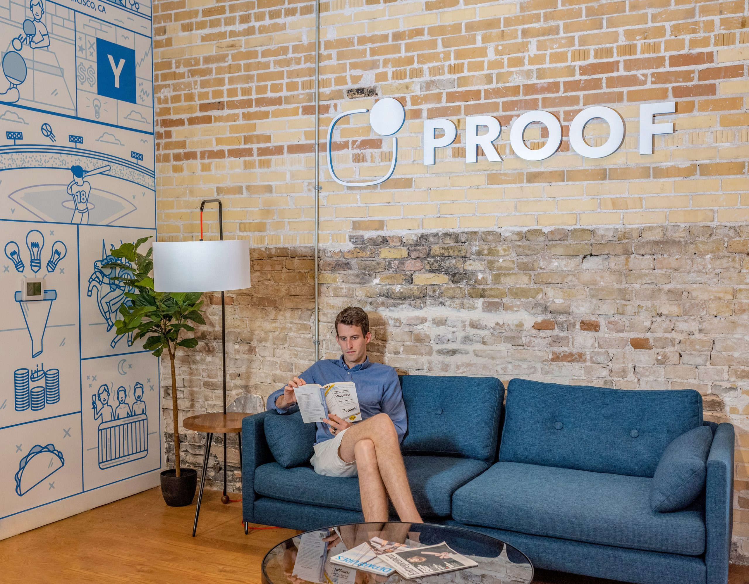 Image of man sitting on a couch reading with the word Proof on the wall above him